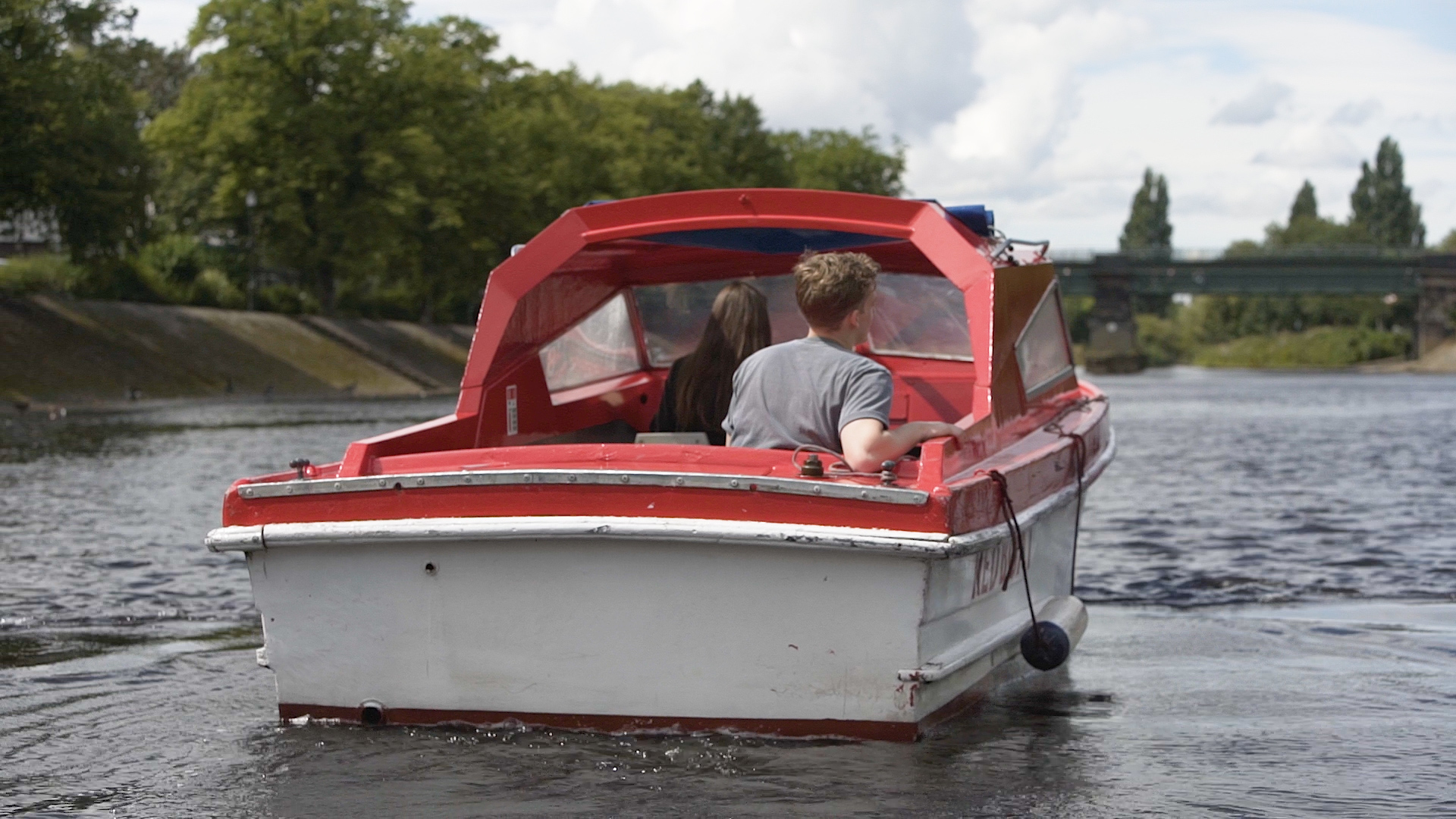 A Young Couple are Driving A self-drive red boat from City Cruises York