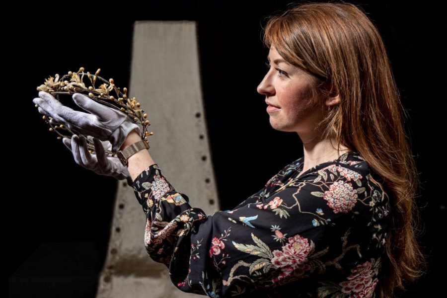 Image of a curator holding up an orange blossom crown from the Becoming The Yorkshire Princess Exhibition