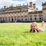 A young girl laying on the grass in front of Harewood House