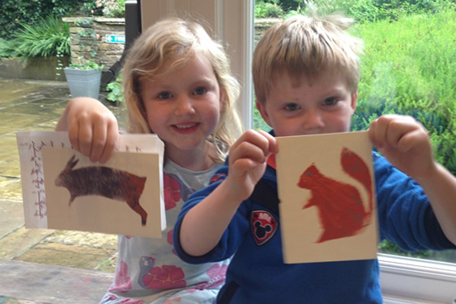 Children holding up drawings of woodland animals that they have created at Bronte Parsonage Museum